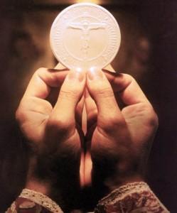 eucaristia fra le mani in elevazione scorniciata