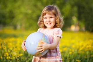 Happy little girl holding globe